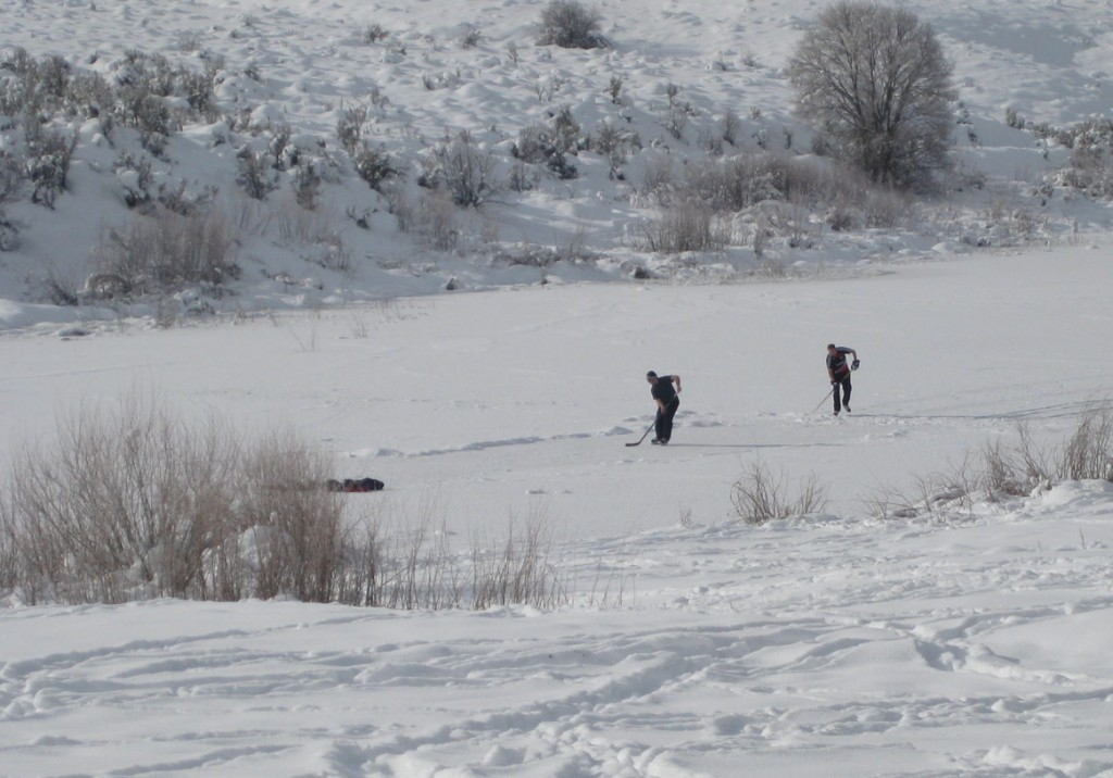A couple guys practicing some hockey moves on the frozen lake below Chair Hill.