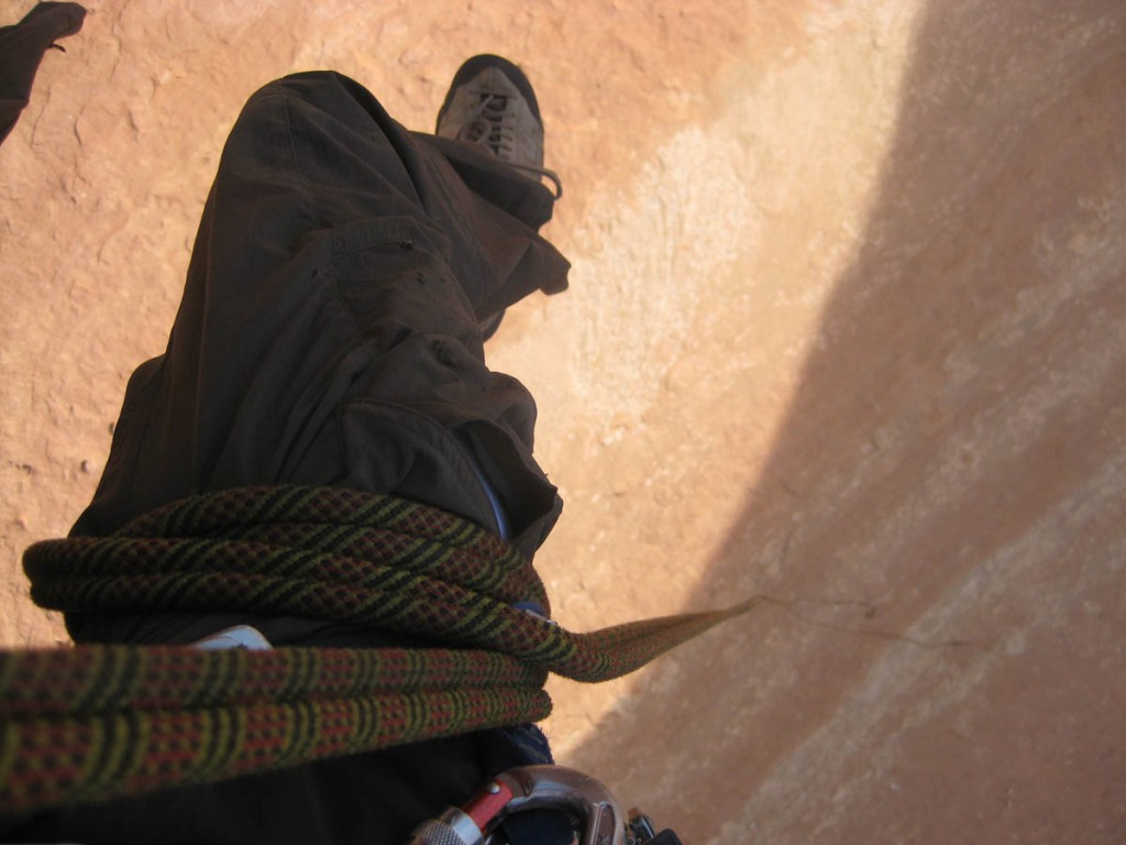 Looking down mid-rappel. Wrapping the rope around your leg a few times lets you hang hands-free while rappelling.