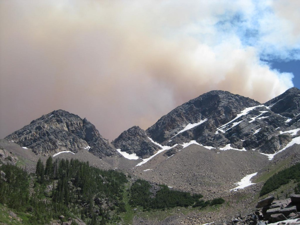 Smoke from a massive fire on a nearby mountain hovering over Sunrise Peak.